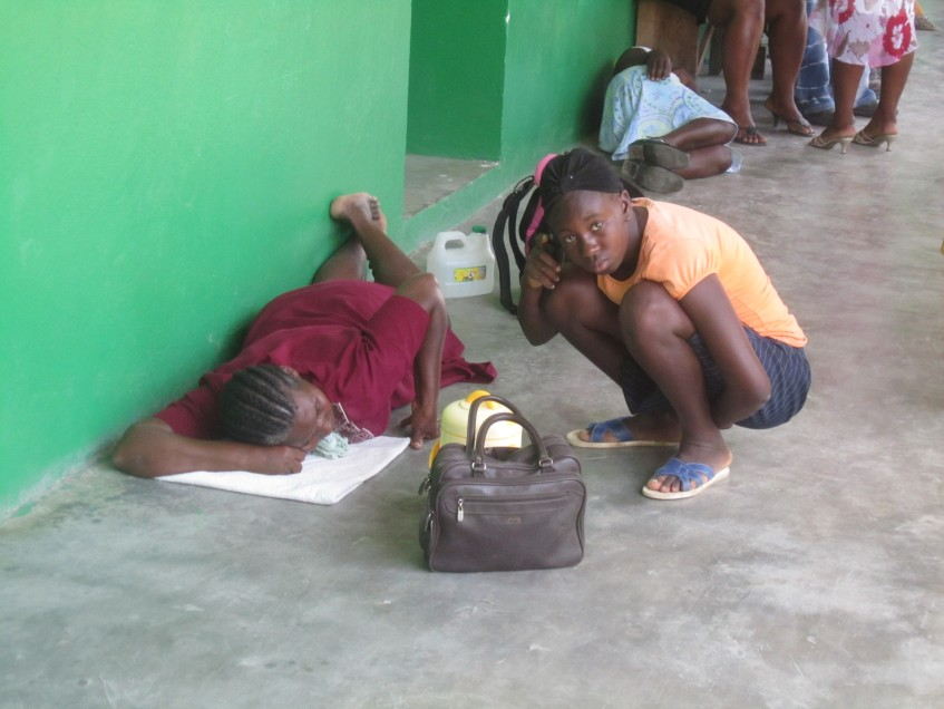 Patients lie on the ground outside St. Therese Hospital in Hinche waiting to see a doctor.