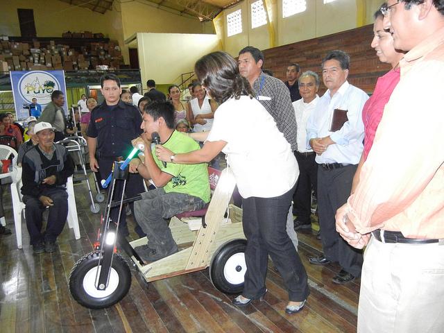 Mrs. Jimena Britos presents PET cart to young Daniel Vargas, who has Cerebral Palsey